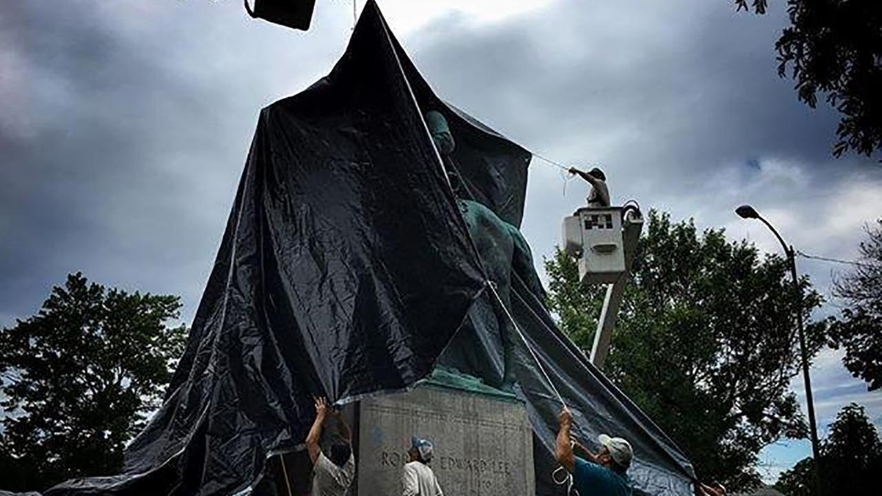 Workers drape a black tarp over the Robert E. Lee statue in Charlottesville, Virginia, Wednesday August 23, 2017.