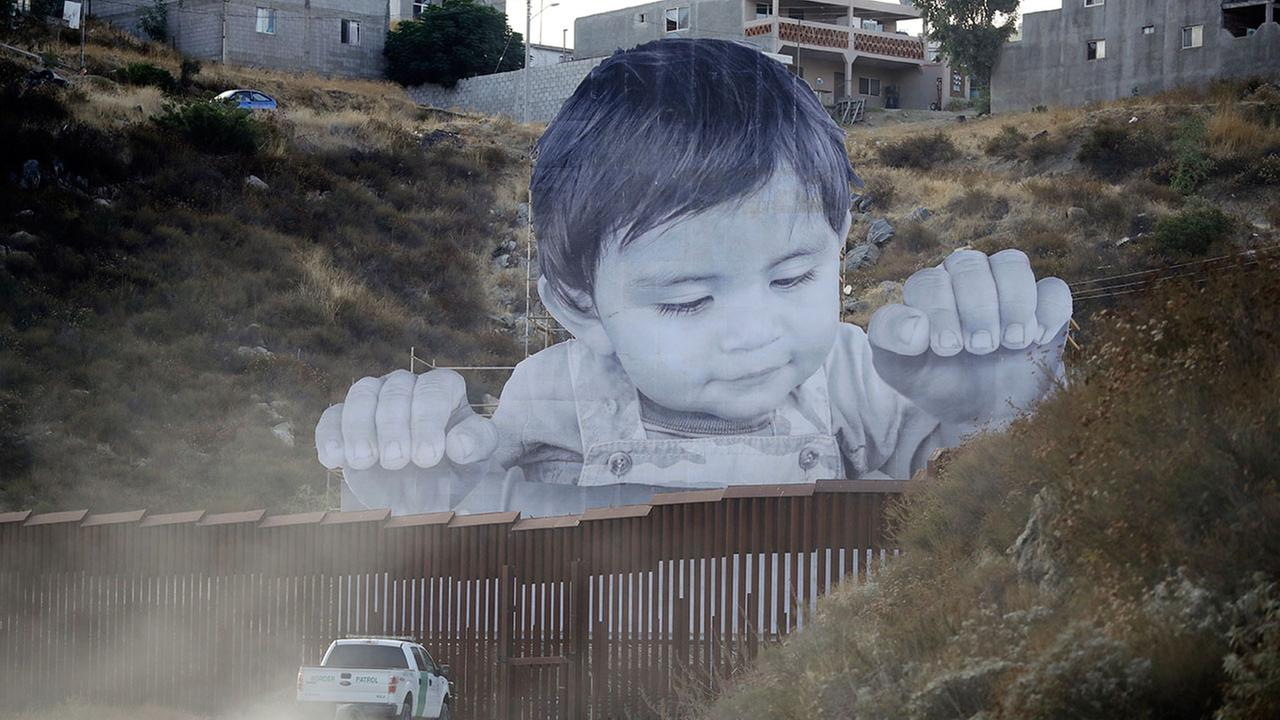 A U.S. Border Patrol vehicle drives in front of a mural in Tecate, Mexico, just beyond a border barrier