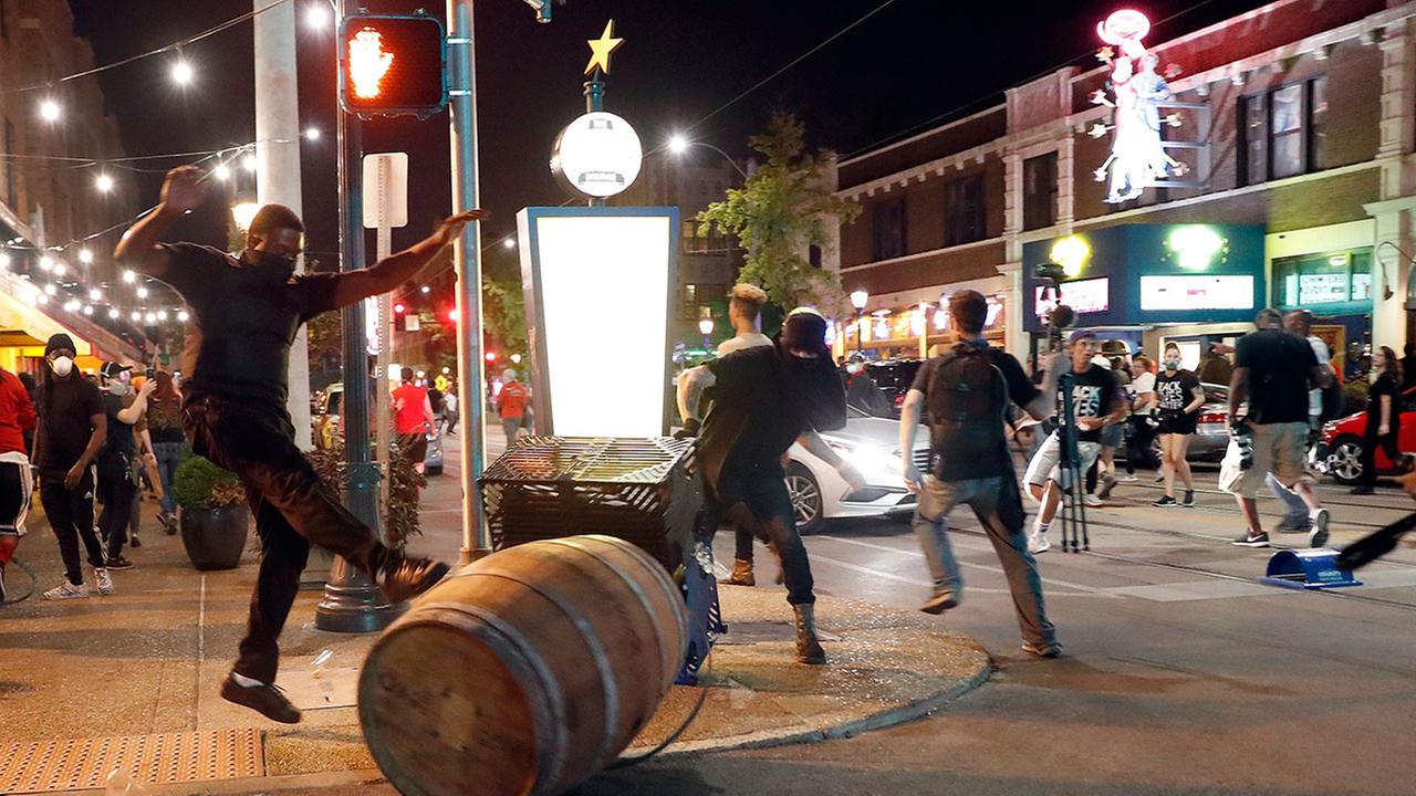 Protesters overturn trash cans as police try to clear a violent crowd Saturday, Sept. 16, 2017, in University City, Mo. Earlier, protesters marched peacefully in response to a not guilty verdict in the trial of former St. Louis police officer Jason Stockl