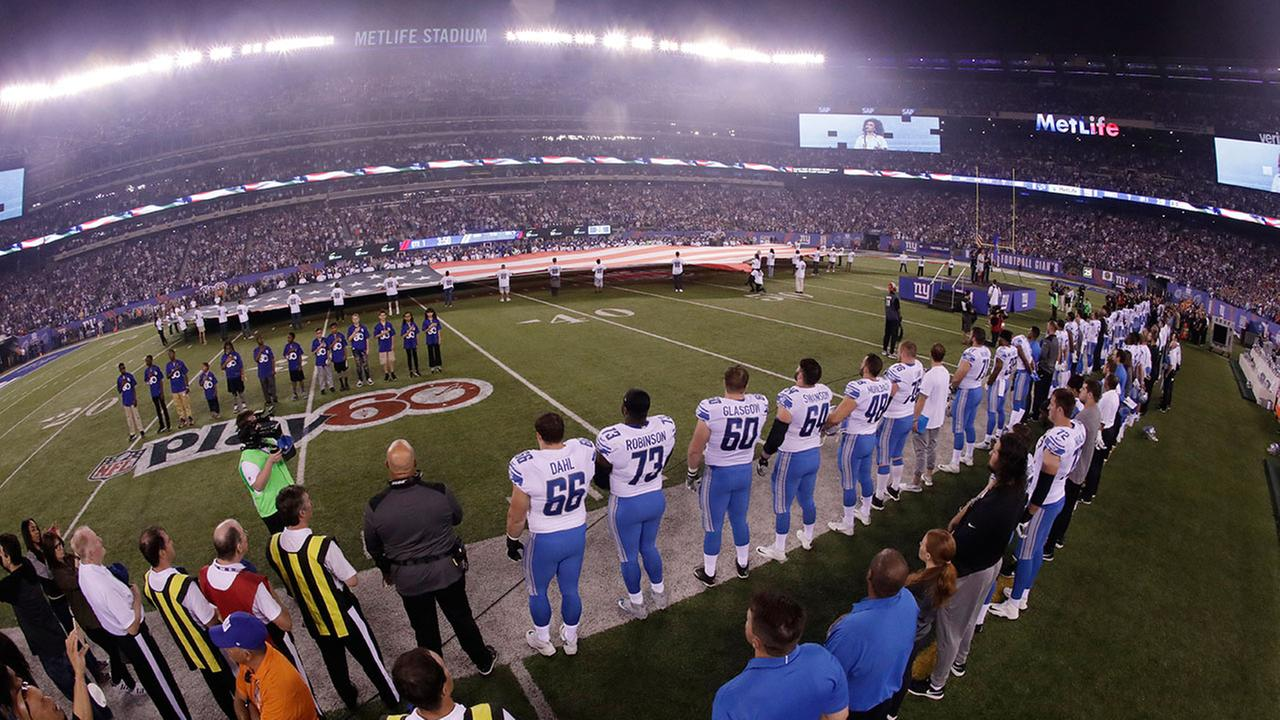 The Detroit Lions stand during the playing of the national anthem before an NFL football game .