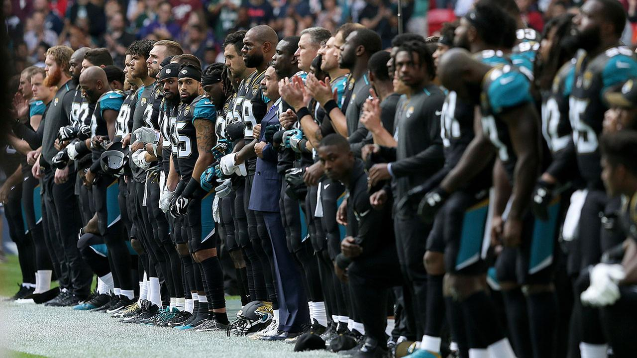 Jacksonville Jaguars owner Shahid Khan, center, joins arms with players as some kneel down