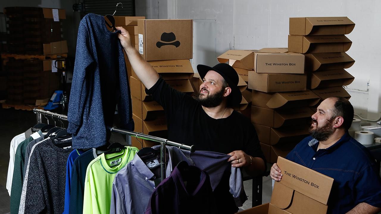 Co-owners Daniel Franzese, left, and Wil Cuadros select clothes for The Winston Box at their showroom in Gardena, Calif.