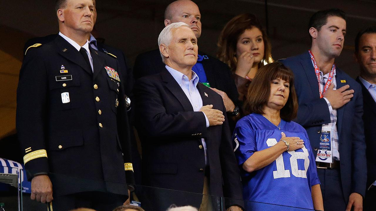 Vice President Mike Pence, front center, stands during the playing of the national anthem before an NFL football