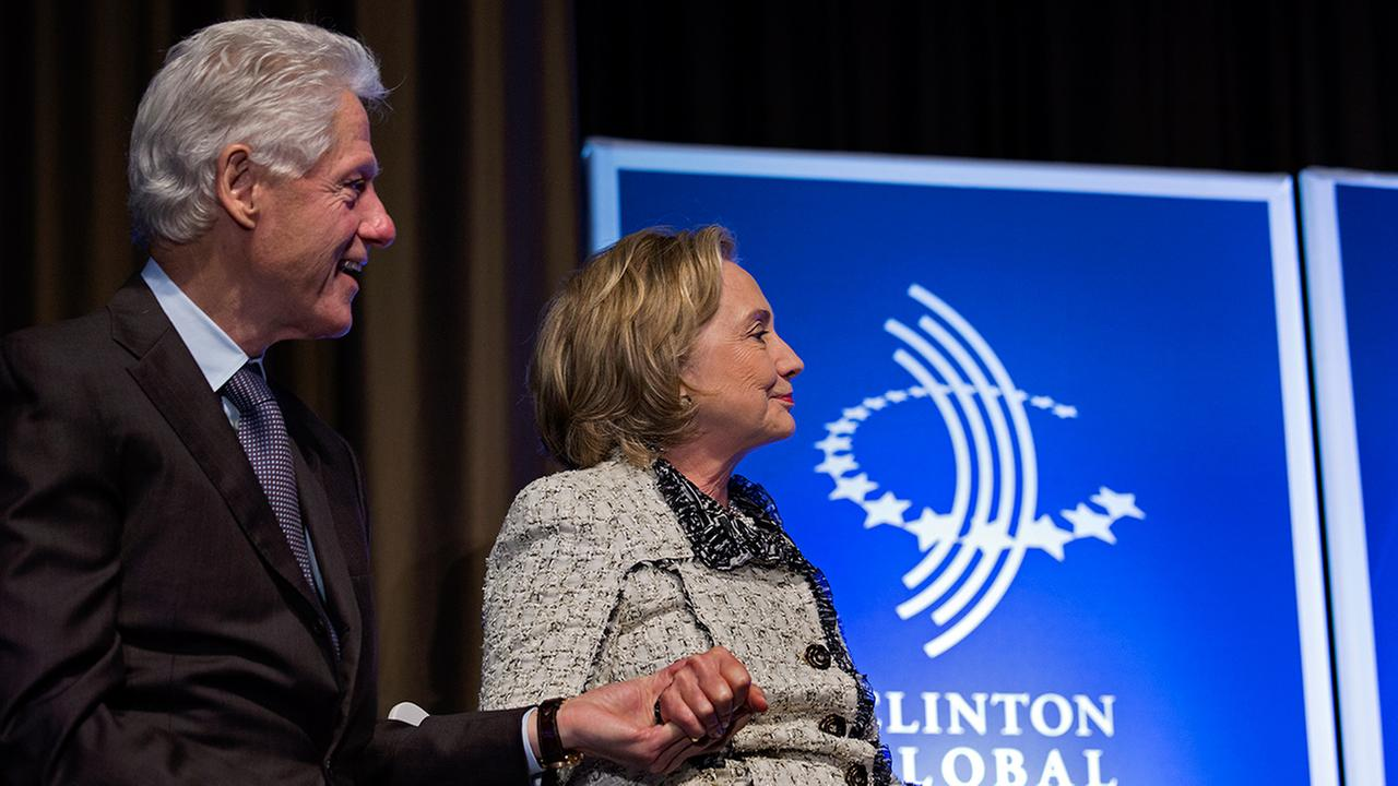 File photo. Former President Bill Clinton and former Secretary of State Hillary Clinton holds hands at the Clinton Global Initiative.