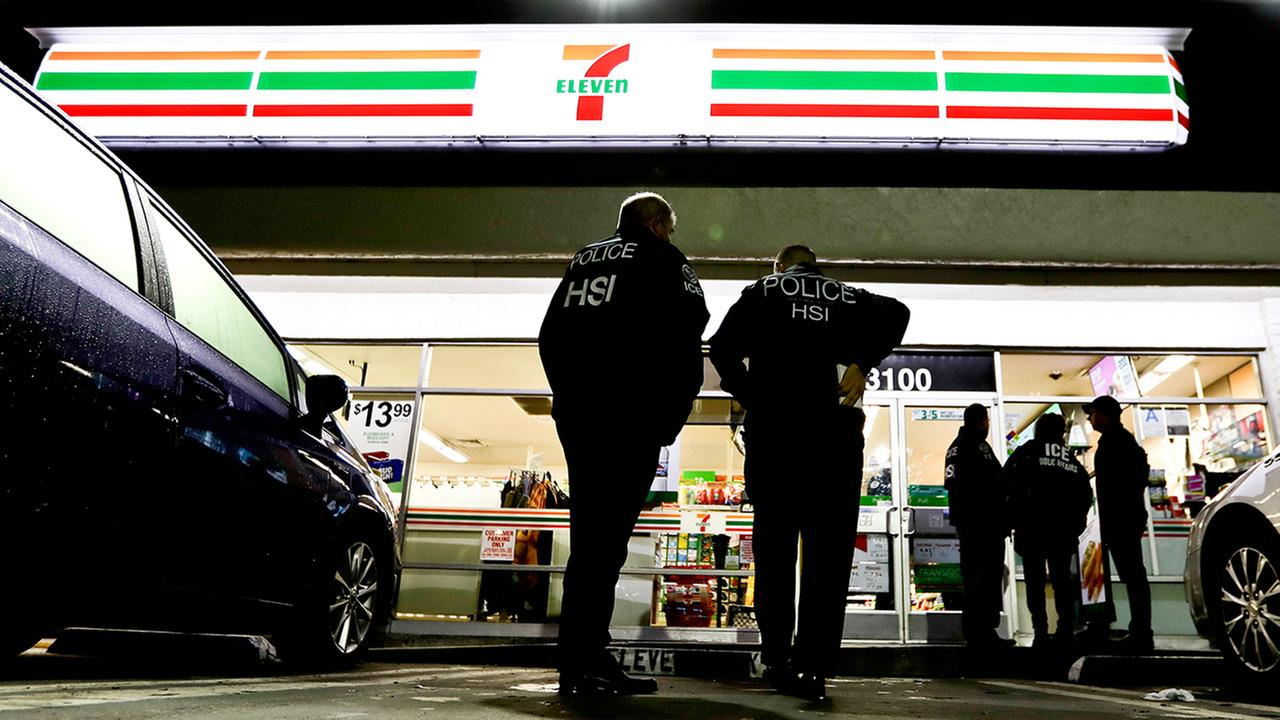 U.S. Immigration and Customs Enforcement agents serve an employment audit notice at a 7-Eleven convenience store Wednesday, Jan. 10, 2018, in Los Angeles.