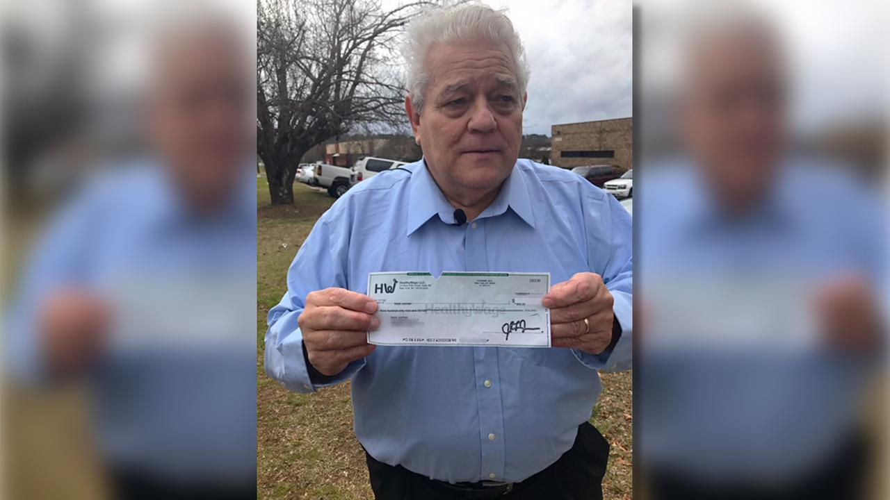 Frank Norman shows off the check he received for losing weight and keeping it off.