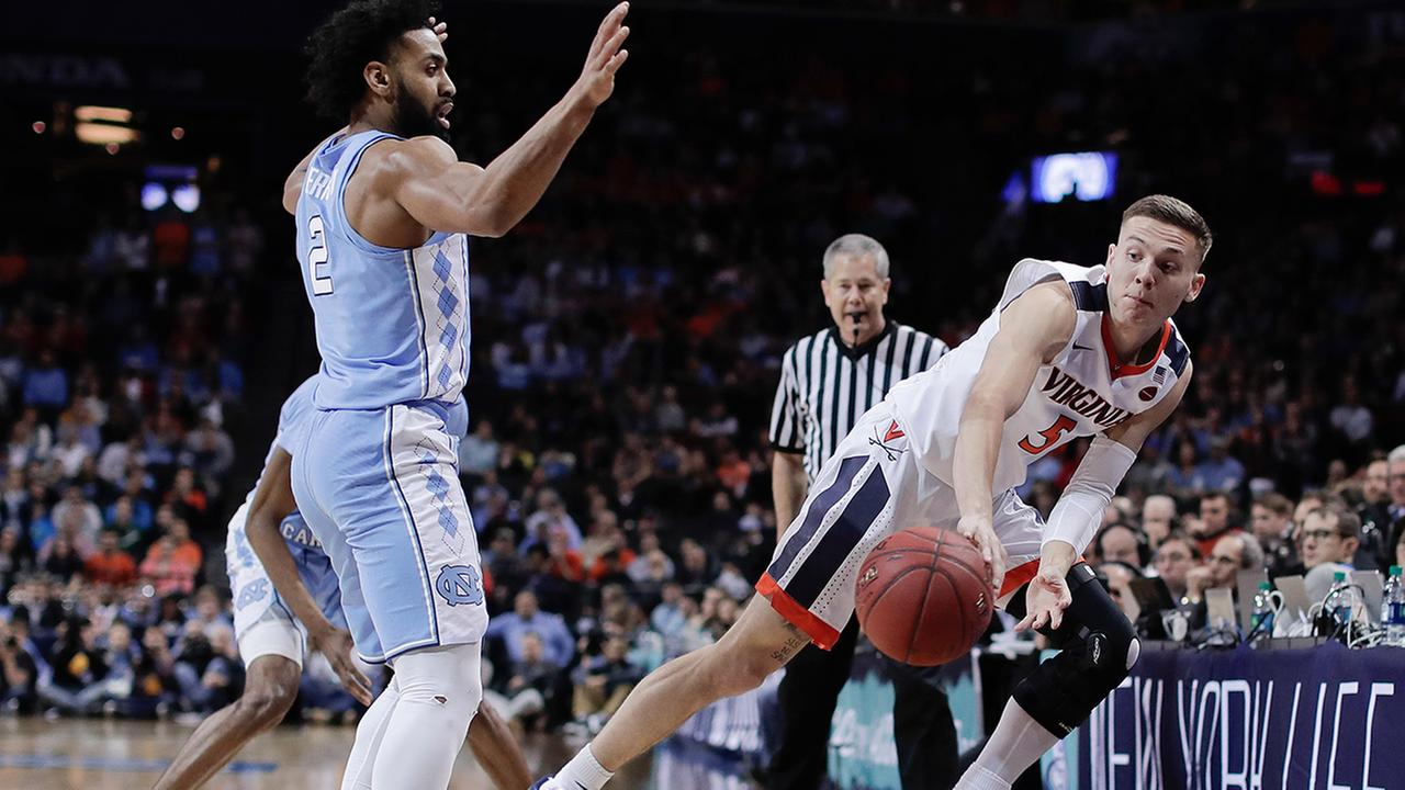 Virginia guard Kyle Guy (5) saves the ball from going out of bounds as North Carolina guard Joel Berry II (2) looks on.