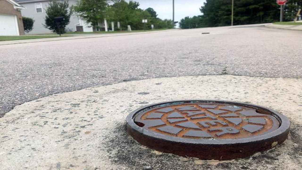 Protruding manhole covers, incomplete sidewalks and storm water drains have left a local subdivision in limbo.