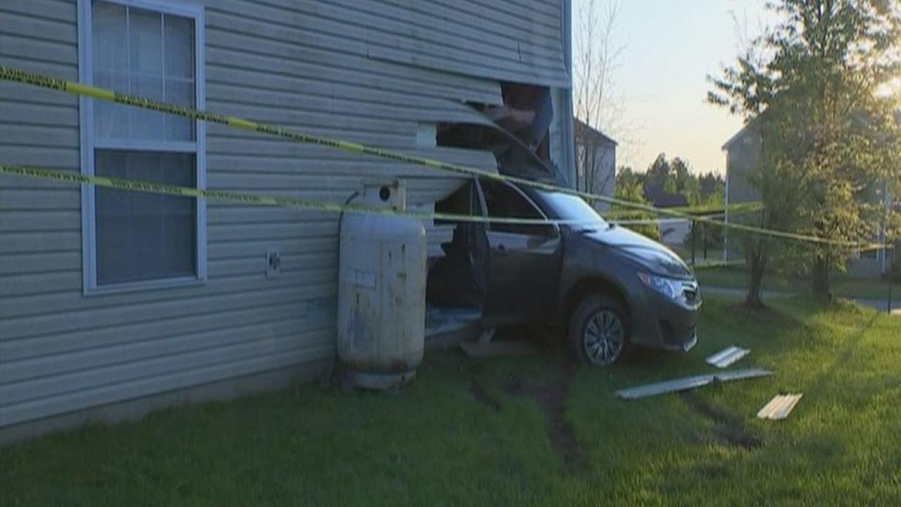 A woman backed her car into a house on Sunday morning