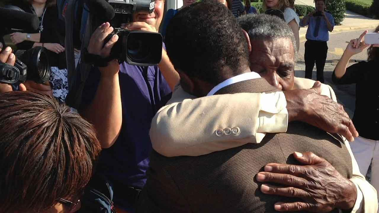 James McCollum, facing camera, embraces his son Henry following the younger mans release from Central Prison in Raleigh, N.C., on Wednesday, Sept. 3, 2014.
