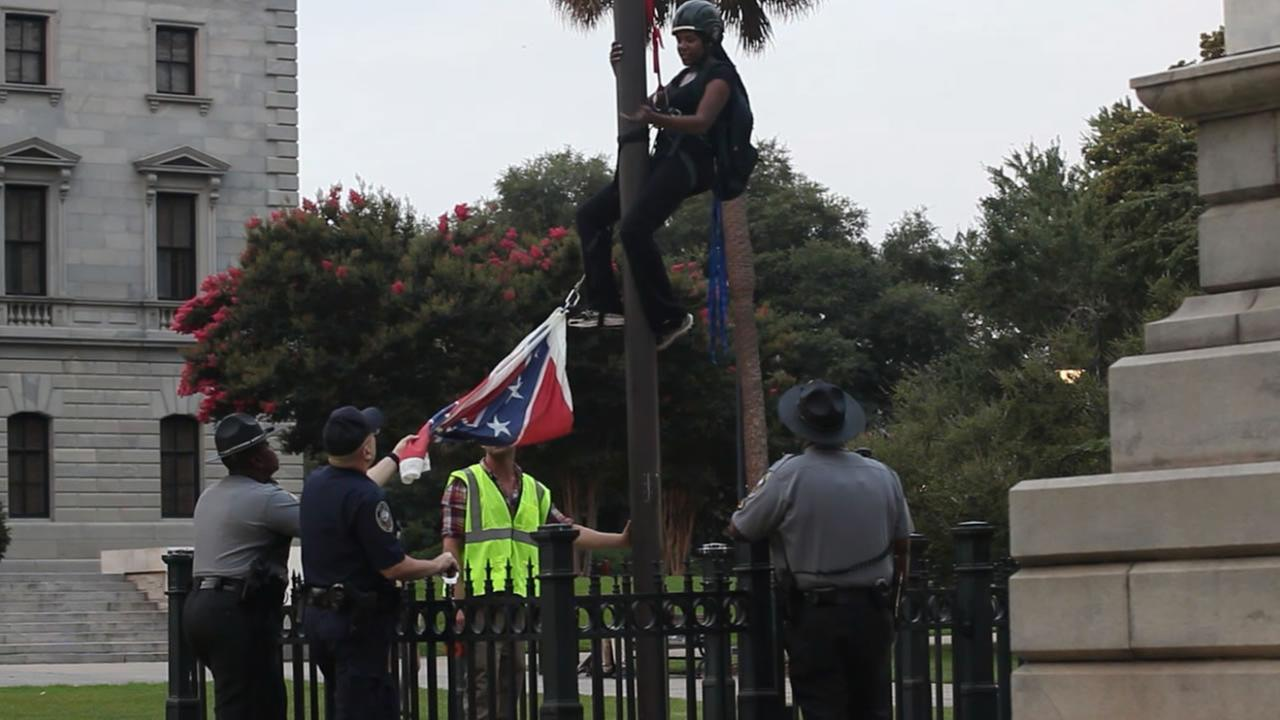 Brittany Ann Byuarim Newsome removes the Confederate flag from a monument at the South Carolina statehouse.