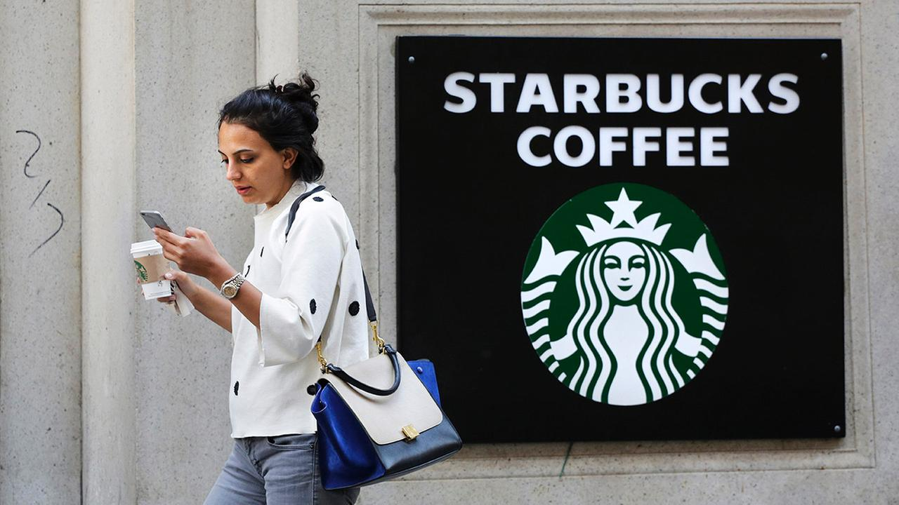 A woman walks out of a Starbucks Coffee with a beverage in hand