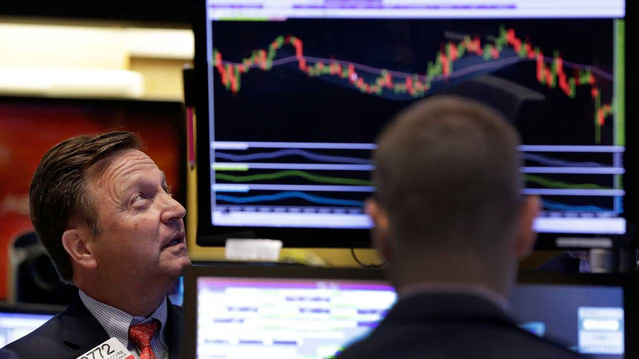 Specialist Thomas Facchine, left, works on the floor of the New York Stock Exchange, Tuesday, Sept. 1, 2015.
