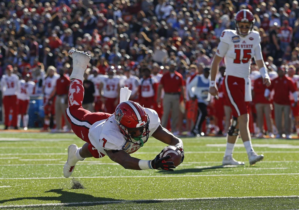 <div class='meta'><div class='origin-logo' data-origin='AP'></div><span class='caption-text' data-credit='Andres Leighton'>North Carolina State running back Nyheim Hines (7) dives into the end zone to score a touchdown.</span></div>