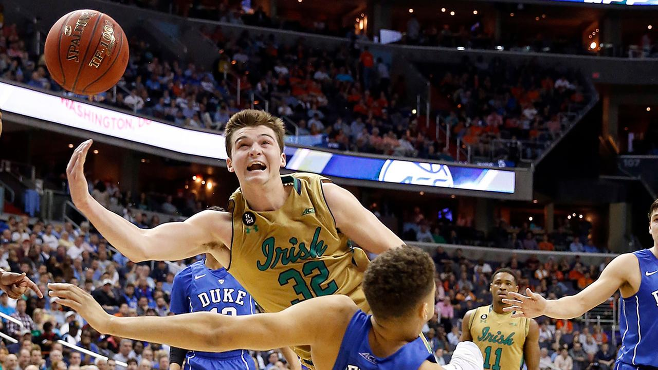 Notre Dame guard Steve Vasturia (32) shoots as he collides with Duke forward Chase Jeter on Thursday at the ACC Tournament.