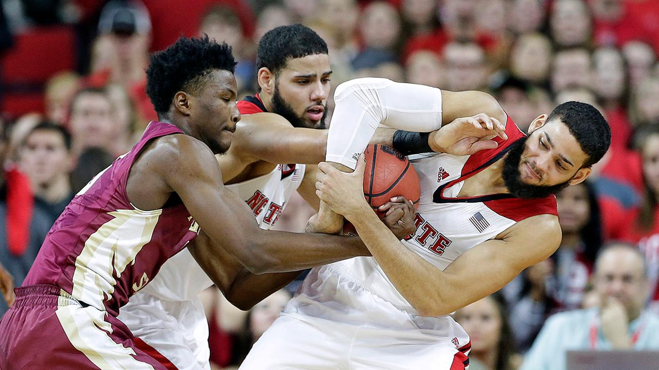 N.C. States Caleb Martin, center, and Cody Martin, right, battle against Florida States Malik Beasley.