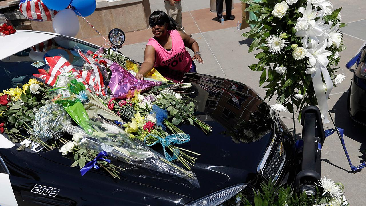 Cynthia Ware places flowers on a make-shift memorial at the Dallas police headquarters, Friday, July 8, 2016, in Dallas.