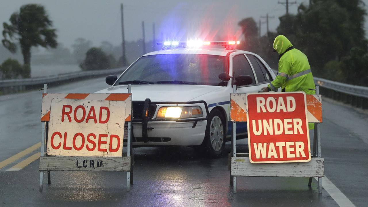 Police block the road entering Cedar Key, Fla. (AP Photo/John Raoux)