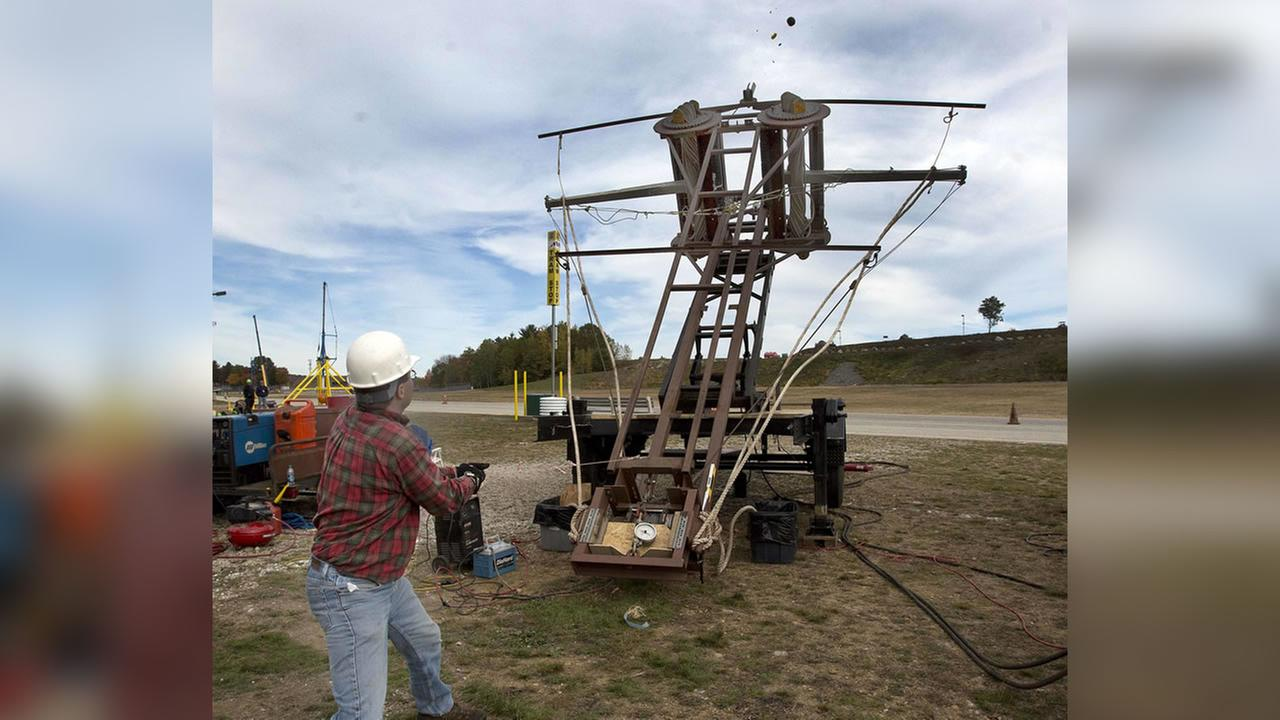 Eric Ludlam, from Framingham, Mass. pulls the trigger on his pumpkin thrower Mista Ballista in Loudon, N.H. (AP Photo/Jim Cole)