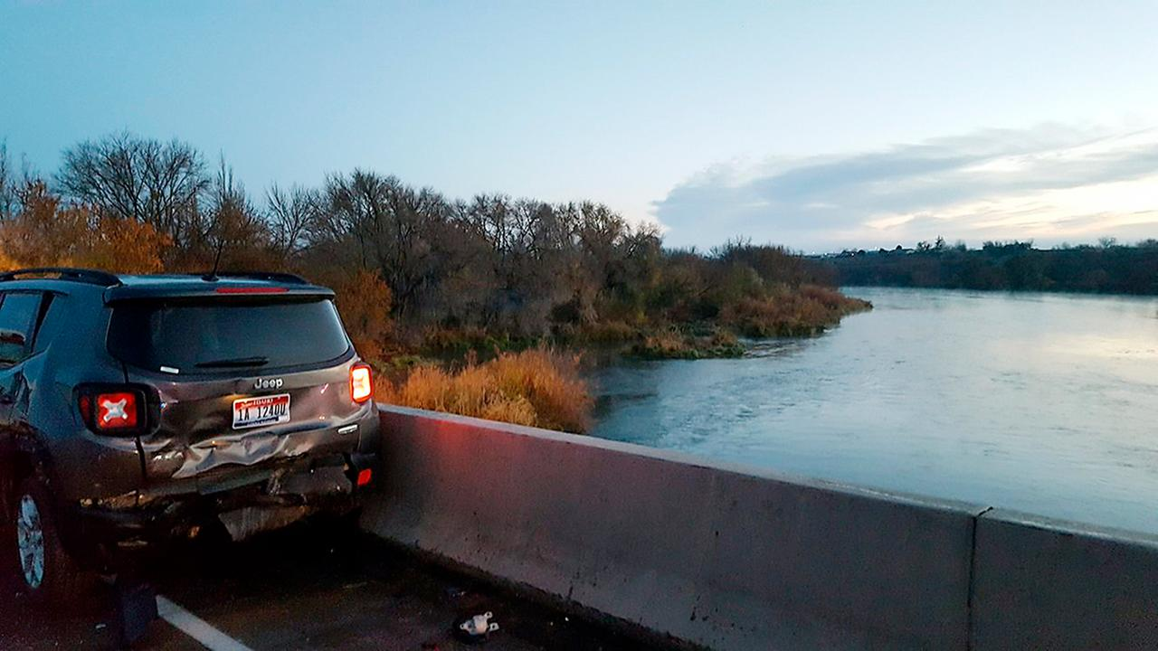A damaged car is shown on an Interstate 84 bridge over the Snake River where Steven Arrasmith was hit by a car and knocked into the icy river below.
