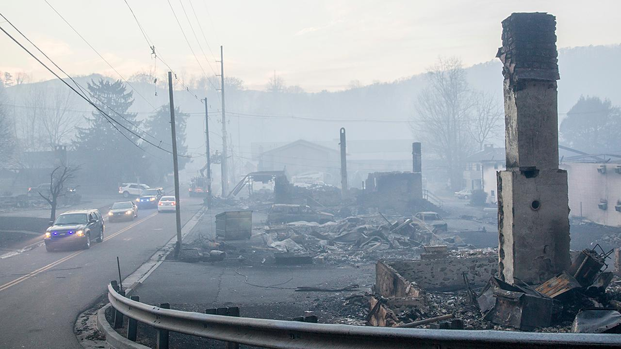 Law enforcement vehicles drive through the smoke near structures destroyed by wildfires in Gatlinburg, Tenn., Tuesday, Nov. 29.