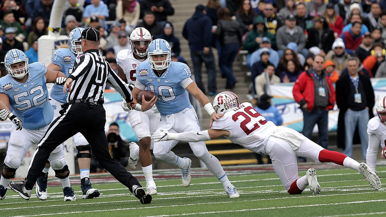 North Carolina quarterback Mitch Trubisky tries to avoid Stanford safety Dallas Lloyd, right, before colliding with the umpire. Trubisky fumbled on the play.