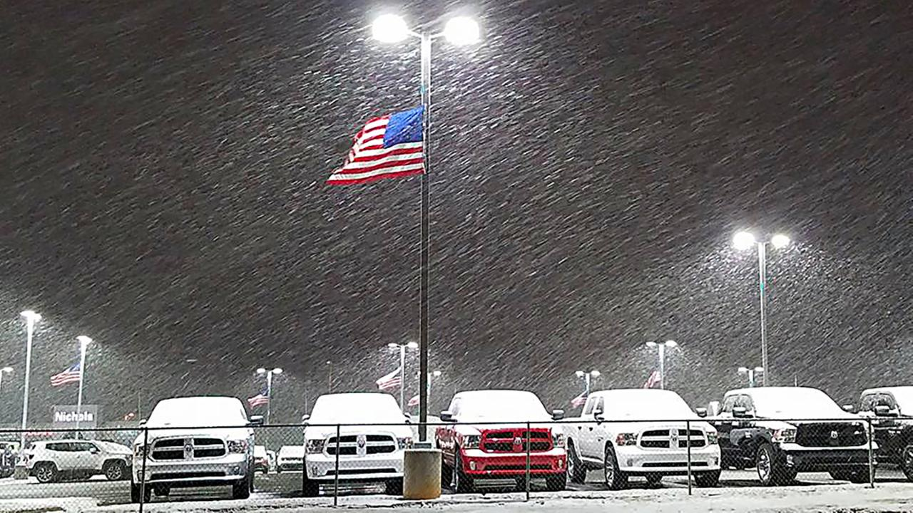 The American flag flies as snow falls at Nichols Dodge in BurlingtonTara Spoonamore - ABC11 Eyewitness