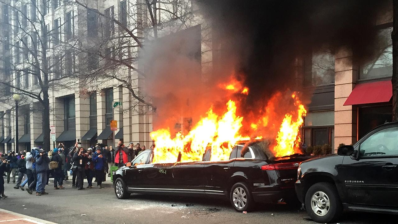 Protesters set a parked limousine on fire in downtown Washington, Friday, during the inauguration of President Donald Trump.