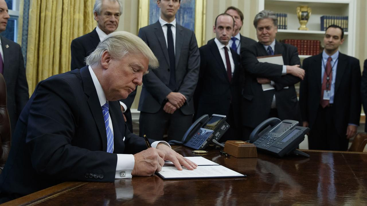 President Donald Trump signs an executive order implementing a federal government hiring freeze, Monday, Jan. 23, 2017.  (AP Photo/Evan Vucci)