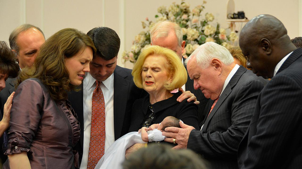 In this 2012 provided by a former member of the church, Word of Faith Fellowship leader Jane Whaley, center, holds a baby with others during a church ceremony in Spindale, N.C.