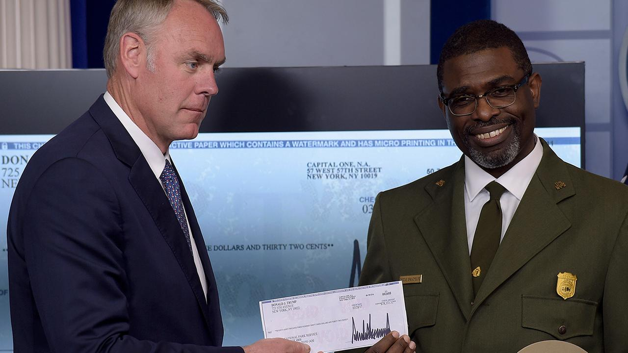 Interior Secretary Ryan Zinke, left, and Harpers Ferry National Historic Park Superintendent Tyrone Brandyburg, hold up a check from President Trumps three-month salary.