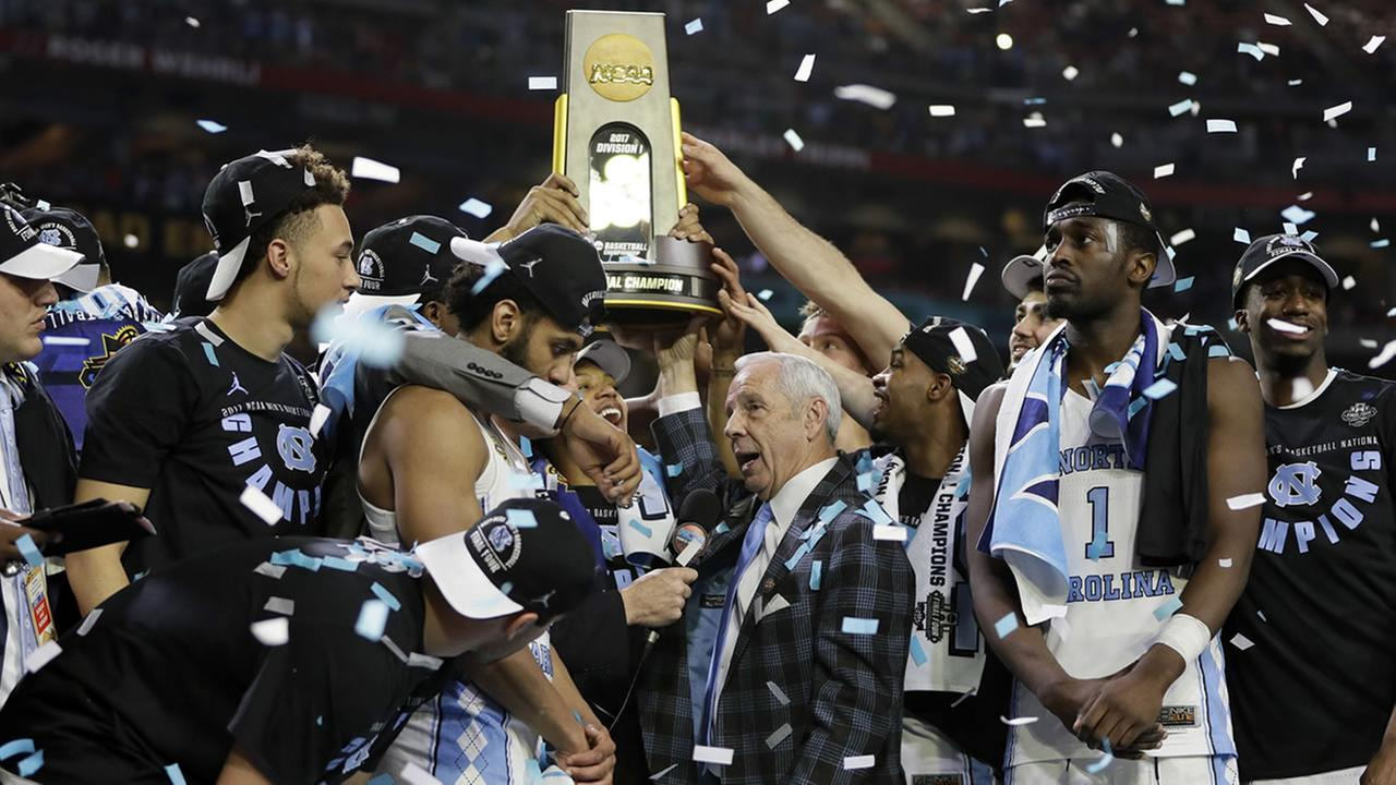 North Carolina head coach Roy Williams is interviewed as his team celebrates (AP Photo/Mark Humphrey)