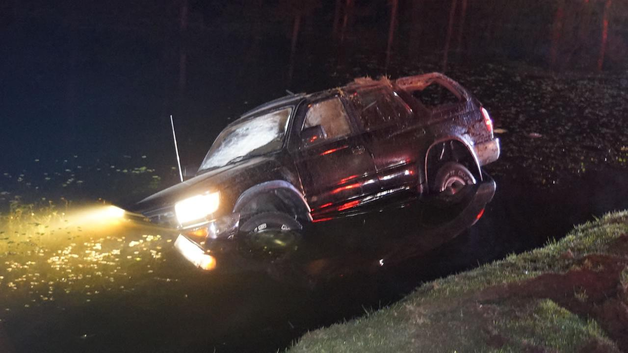The SUV landed in shallow water near the edge of the pond.image courtesy Cypress Pointe Fire