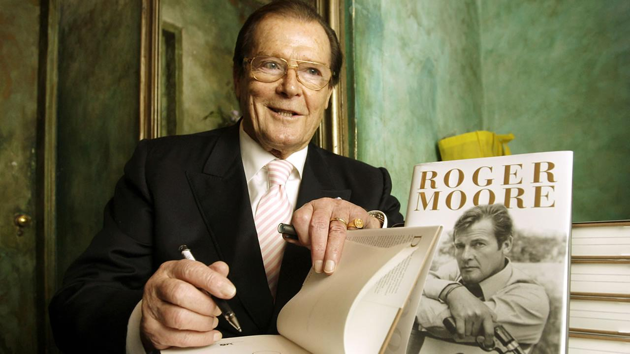British actor Roger Moore signs an autograph in his book The World is My Bond. (AP Photo/Kin Cheung)