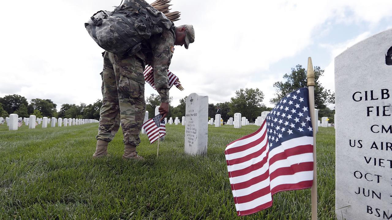 U.S. Army Staff Sgt. Anthony Ellis with the 3d U.S. Infantry Regiment (The Old Guard), places flags at Arlington National Cemetery (AP Photo/Alex Brandon)