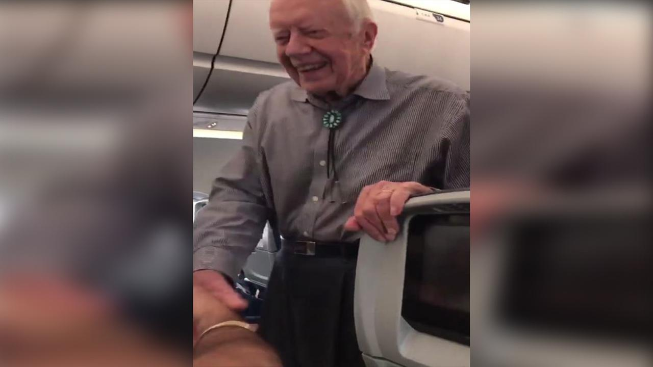 Jimmy Carter shakes hands with passengers on ATL flight