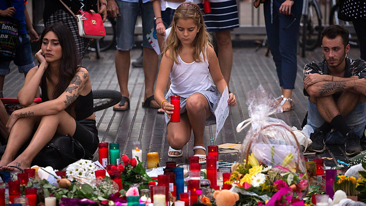 A girl places a candle on a memorial Sunday after a terror attack that killed 14 people and wounded over 120 in Barcelona, Spain.