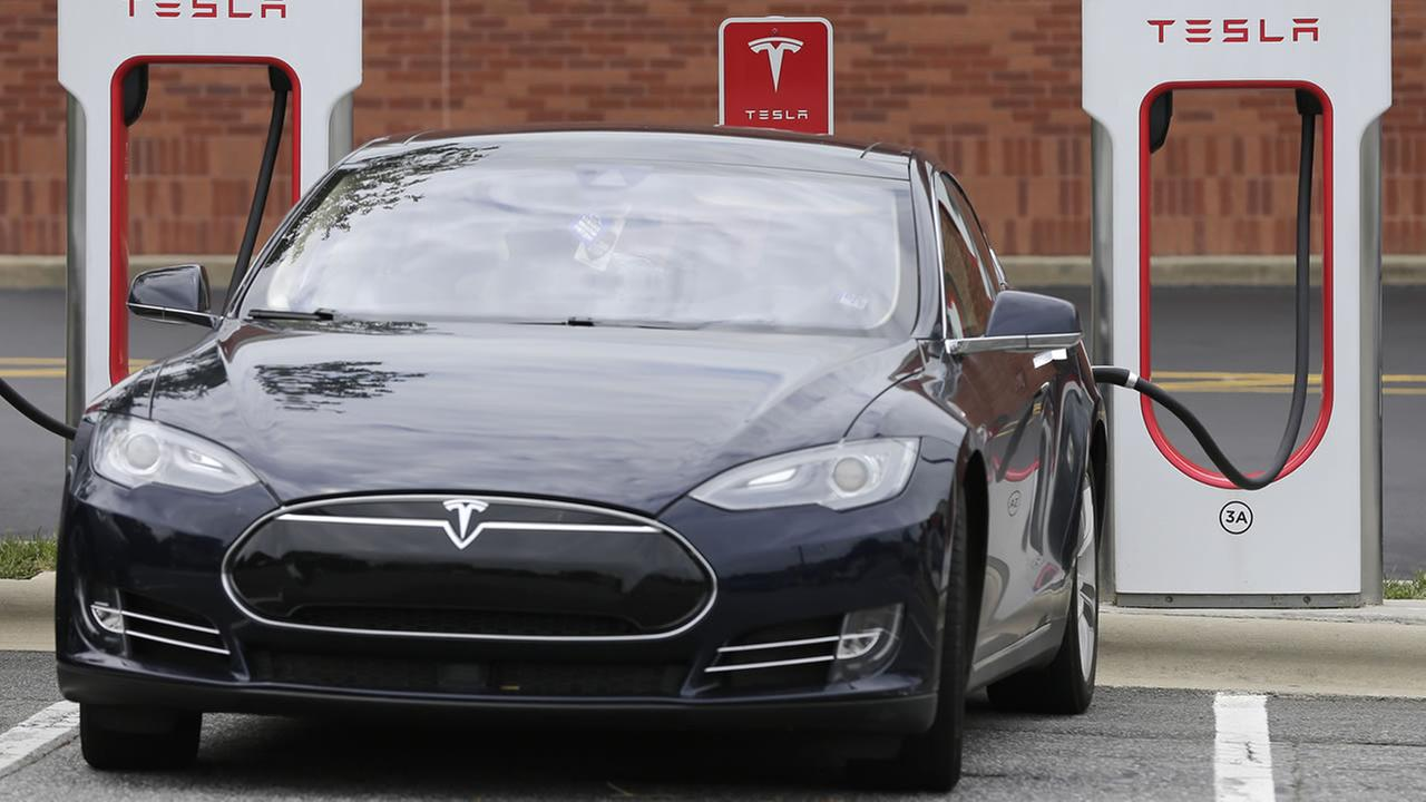 A Tesla car recharges at a charging station at Cochran Commons shopping center in Charlotte. (AP Photo/Chuck Burton)