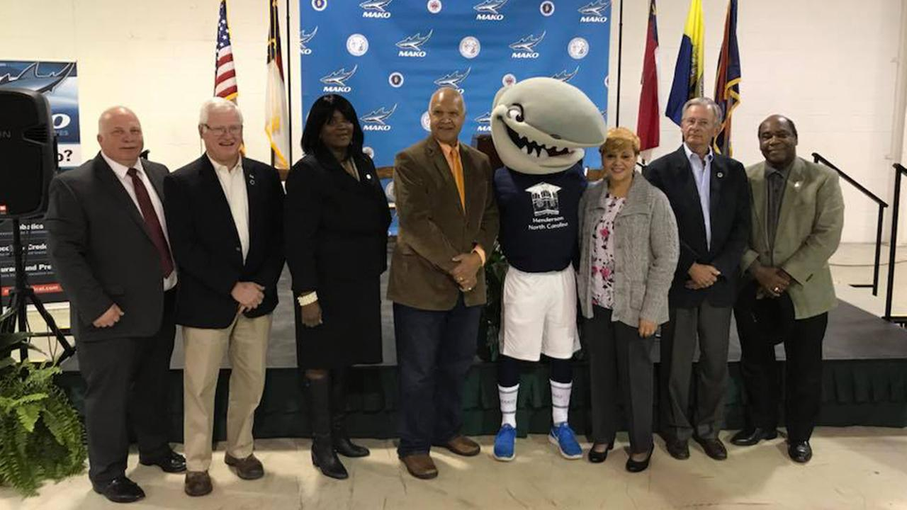 Mikey Mako poses with company and state officials following the announcement