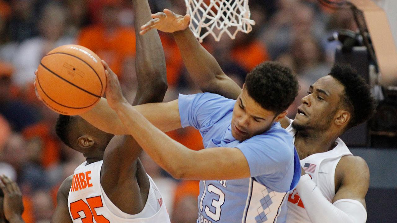North Carolinas Cameron Johnson, center, grabs a rebound from Syracuses Bourama Sidibe, left, and Syracuses Oshae Brissett on Wednesday.
