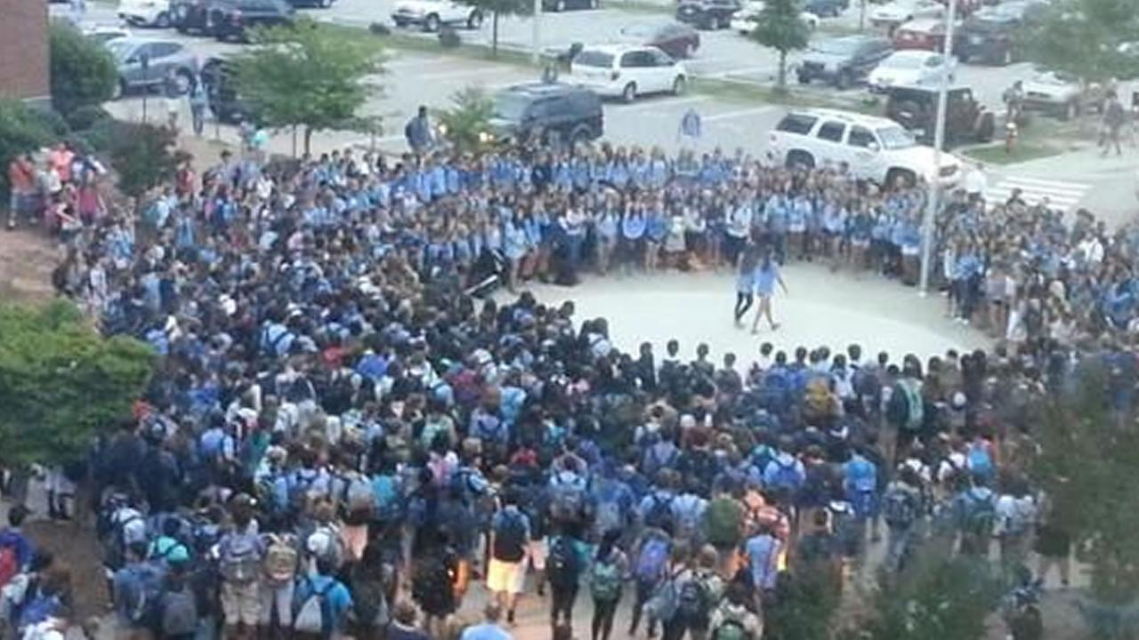 Students gather outside Panther Creek High School for a vigil.