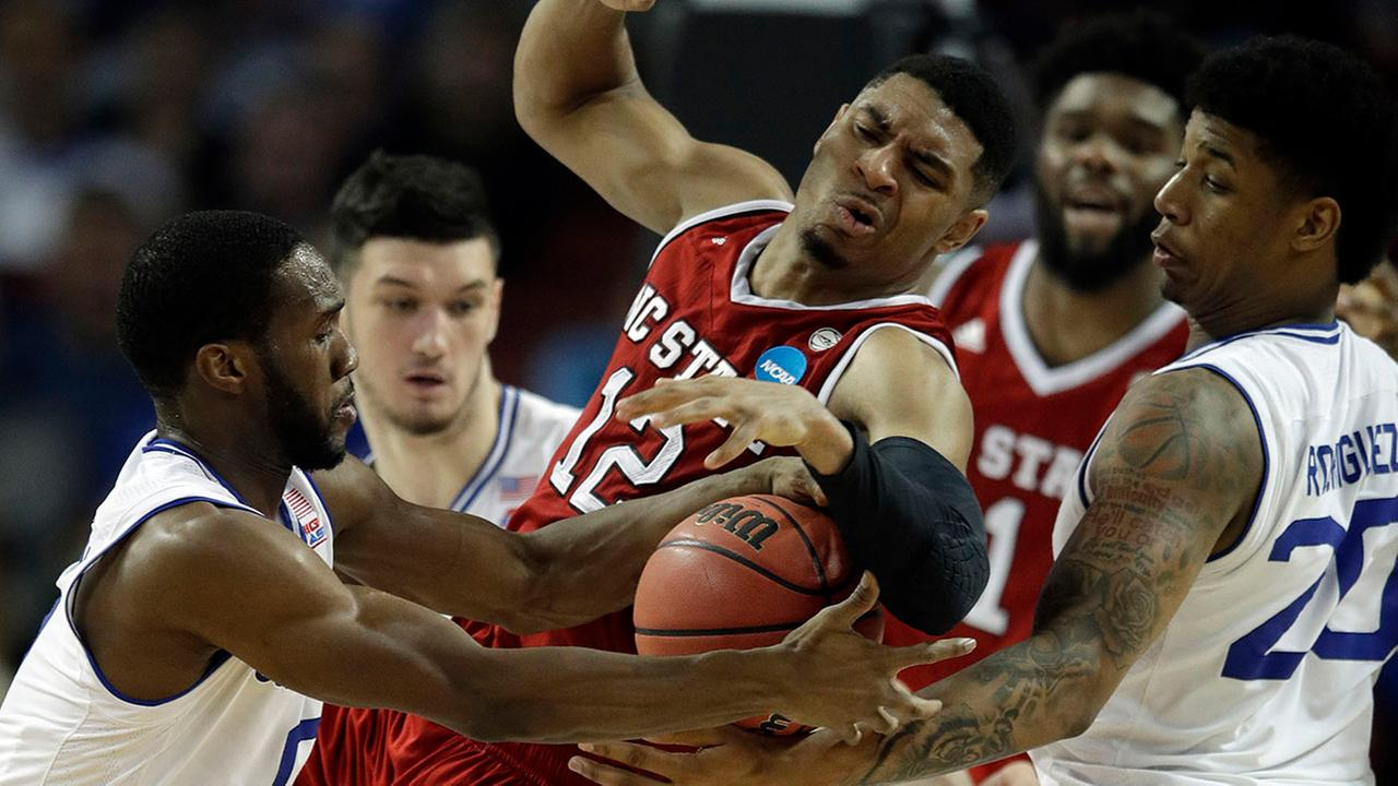 North Carolina State guard Allerik Freeman (12) tries to control a rebound between Seton Hall guard Khadeen Carrington, left, and forward Desi Rodriguez (20).