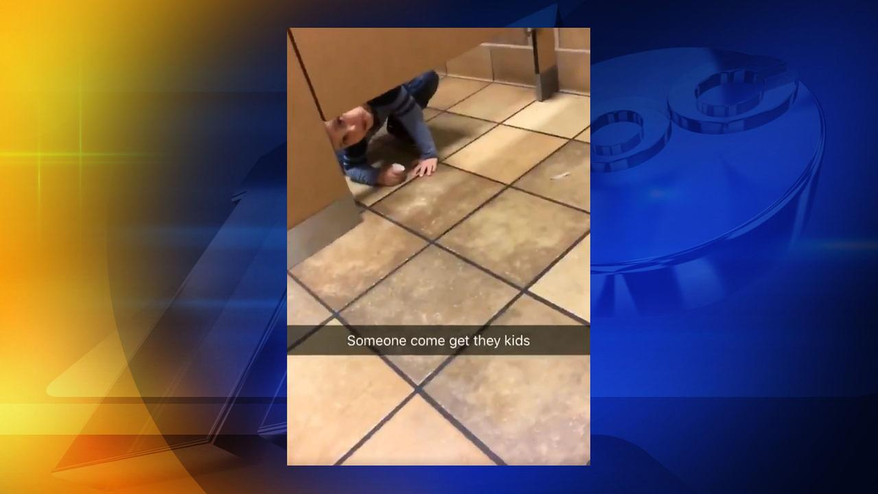 Curious kid crawls under customers stall at Chick-fil-A