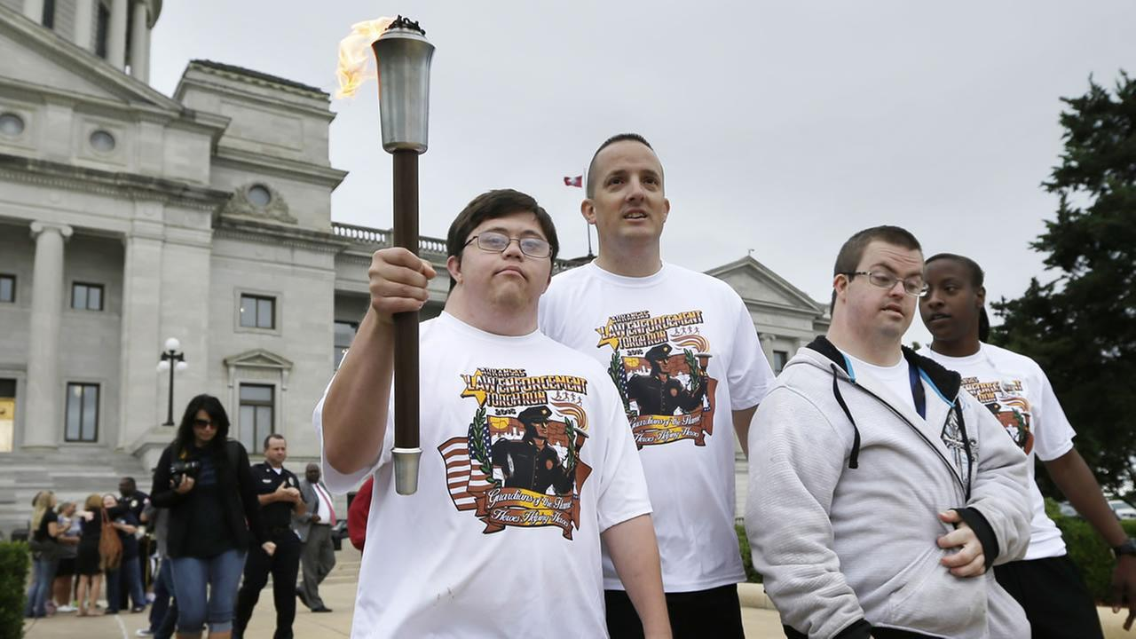 David Dallas, left, carries the Arkansas Special Olympics Torch accompanied by Little Rock police Capt. Heath Helton, center, and other athletes in Little Rock, Arkansas.