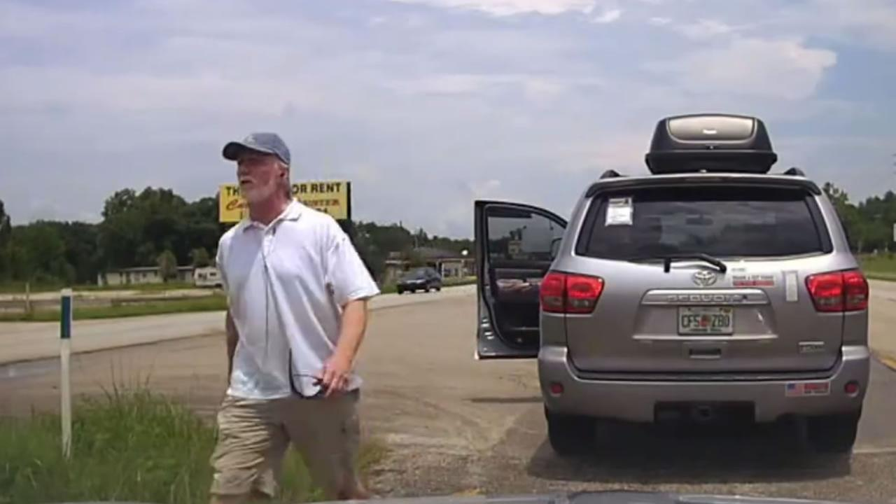 The video shows the man jump out and begin yelling at the officer as he approaches the driver side of the police car.