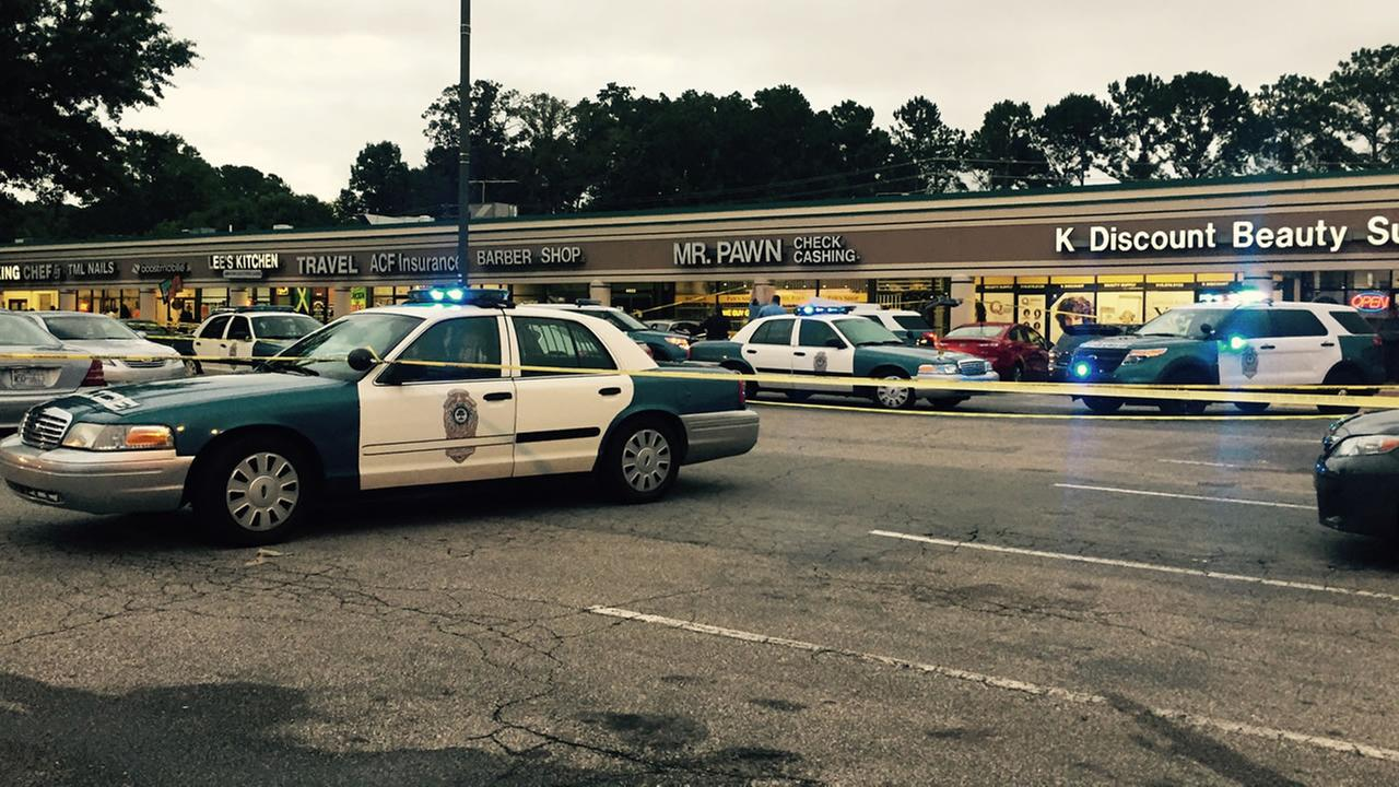 Police investigate a shooting at Mr. Pawn Check Cashing Services