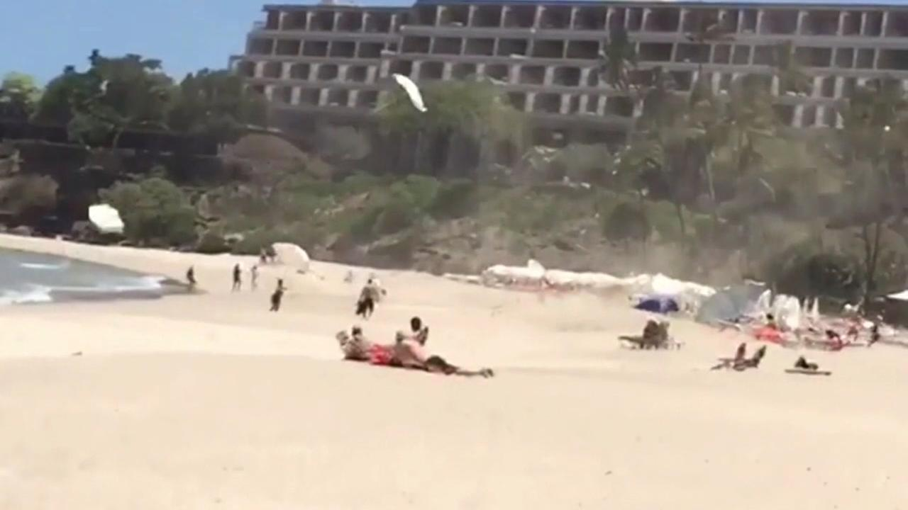 Wind sends beach umbrellas flying
