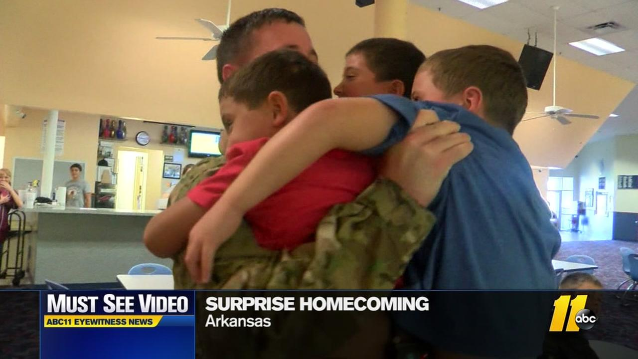 Returning airman gets triple hug from triplets