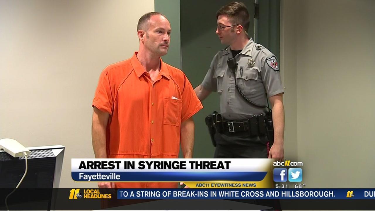 Man arrested in syringe threat
