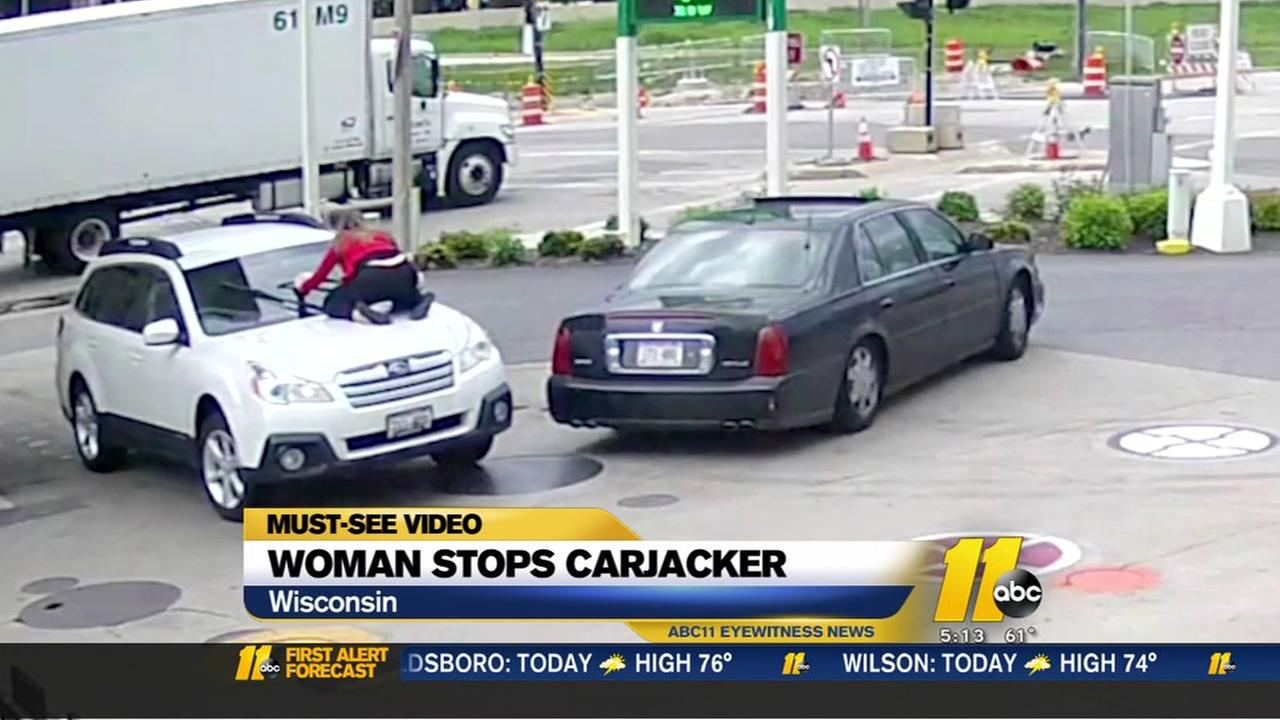 Woman stops carjacker by jumping onto hood